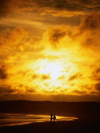 mark-newman-couple-in-silhouette-on-beach-beneath-sunset-isla-santa-cruz-galapagos-ecuador