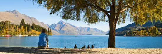 matthew-williams-ellis-panorama-of-tourist-relaxing-by-lake-wakatipu-in-autumn-at-queenstown-otago-new-zealand