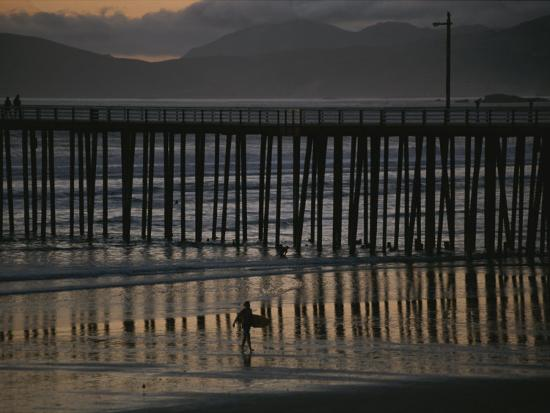 michael-s-lewis-a-surfer-walks-up-the-beach-near-a-pier-at-twilight