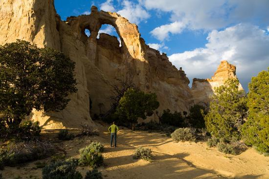 mike-cavaroc-visitor-to-grosvenor-arch-standing-below-eroded-double-arch-grand-staircase-escalante-nm-utah