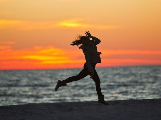 mike-theiss-silhouette-of-a-woman-jumping-in-front-of-a-colorful-beach-sunset