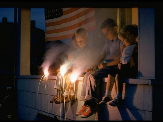 nat-farbman-boys-sitting-on-porch-holding-sparklers-with-us-flag-in-back-during-independence-day-celebration