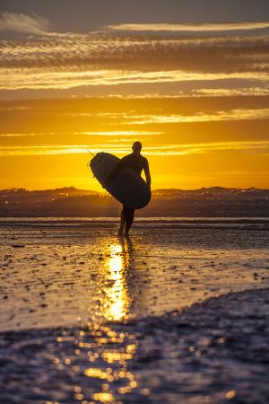 niels-van-gijn-uk-cornwall-polzeath-a-woman-comes-in-from-an-evening-surf-against-a-stunning-sunset