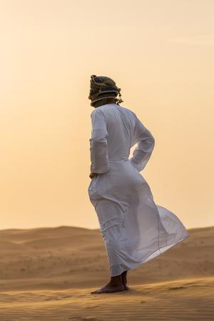 nigel-pavitt-oman-wahiba-sands-an-omani-guide-enjoys-the-sunset-on-sand-dunes-in-wahiba-sands