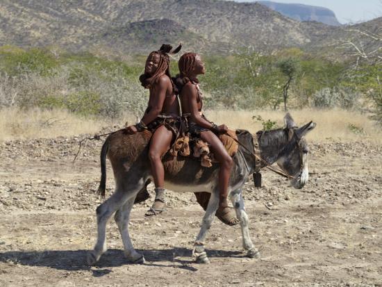 nigel-pavitt-two-happy-himba-girls-ride-a-donkey-to-market-namibia