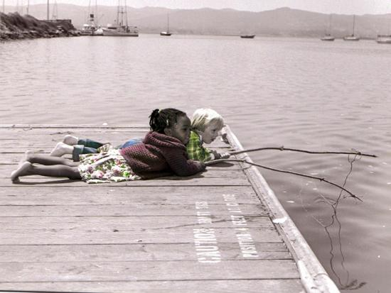 nora-hernandez-boy-and-girl-laying-on-dock-fishing