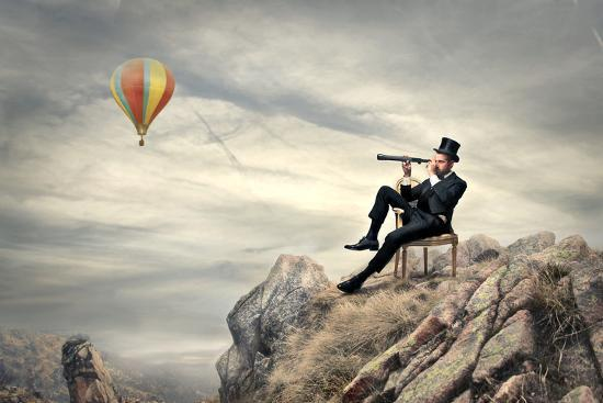 olly2-rich-businessman-sitting-on-a-chair-in-the-mountain-looking-the-landscape-with-spyglass