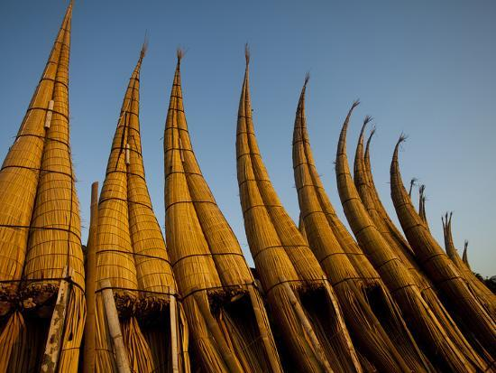 patrick-brooks-brandenburg-traditional-reed-fishing-boat-still-in-use-today-lined-up-during-sunset-in-huanchaco-peru