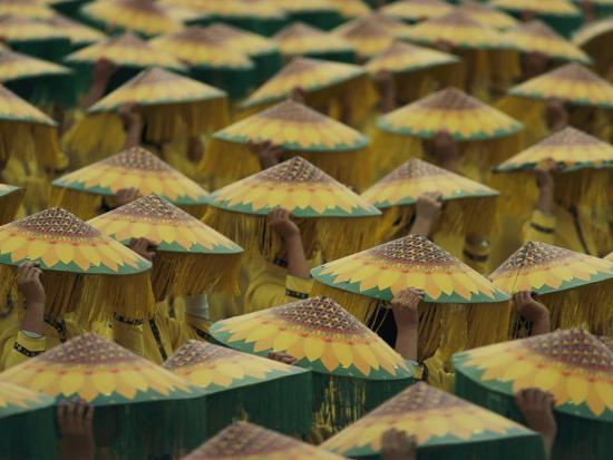 paul-chesley-parade-participants-cover-their-heads-with-coolie-hats-painted-to-look-like-sunflowers