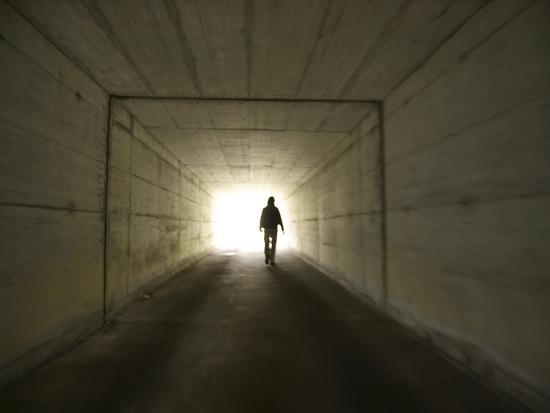 person-walking-through-tunnel-towards-light