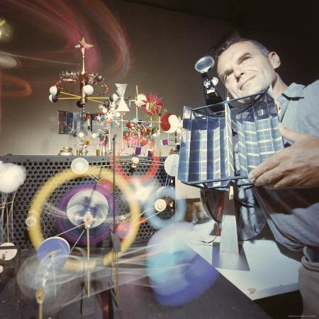 ralph-crane-architect-designer-charles-eames-with-engine-that-generates-solar-power-to-run-toys-surrounding-him