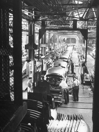 ralph-morse-employees-working-on-cars-as-they-move-down-assembly-line
