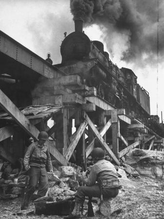 ralph-morse-gi-infantry-guards-keeping-warm-by-a-fire-next-to-an-army-engineer-built-railroad-bridge