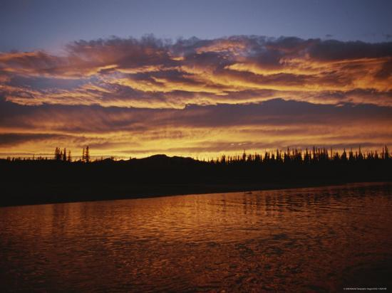 raymond-gehman-an-intense-sunset-colors-clouds-and-the-water-of-the-mackenzie-river