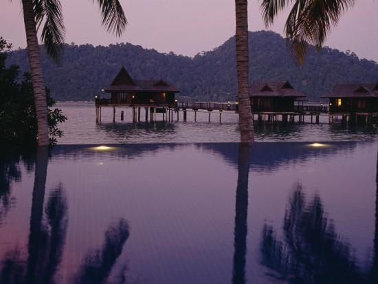 reflections-in-a-pool-and-traditional-malaysian-houses-on-stilts