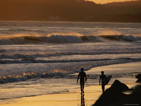 rich-reid-surfers-are-silhouetted-by-the-sunset-on-a-beach-in-santa-barbara