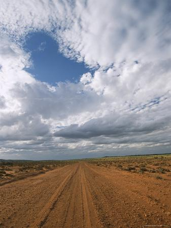 richard-nowitz-view-of-clouds-filling-the-sky-over-a-dirt-road