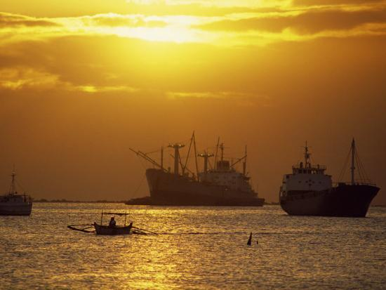 robert-francis-cargo-ships-and-outrigger-canoe-in-manila-bay-at-sunset-in-the-philippines-southeast-asia