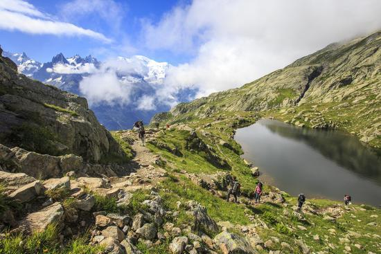 roberto-moiola-low-clouds-and-mist-around-grandes-jorasses-while-hikers-proceed-on-lac-de-cheserys-french-alps