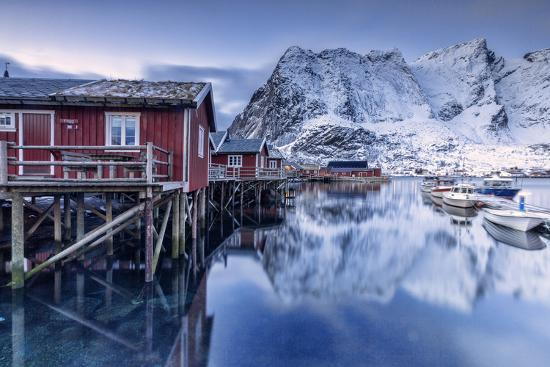 roberto-moiola-snowy-mountains-and-the-typical-red-houses-reflected-in-the-cold-sea-at-dusk
