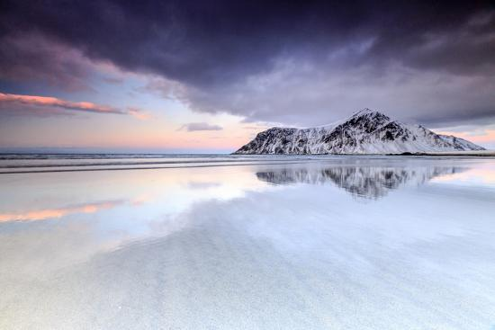 roberto-moiola-sunset-on-skagsanden-beach-surrounded-by-snow-covered-mountains-reflected-in-the-cold-sea