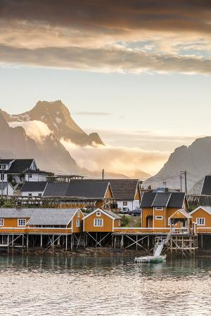 roberto-moiola-sunset-on-the-fishing-village-framed-by-rocky-peaks-and-sea-sakrisoya-nordland-county