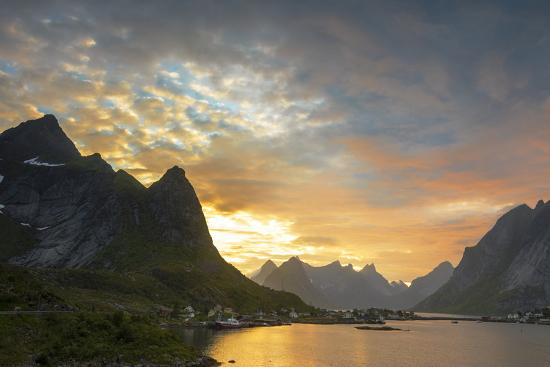 roberto-moiola-sunset-on-the-fishing-village-surrounded-by-rocky-peaks-and-sea-reine-nordland-county