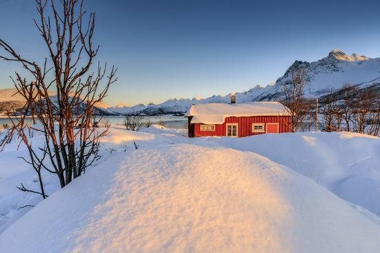 roberto-moiola-the-winter-sun-illuminates-a-typical-norwegian-red-house-surrounded-by-fresh-snow