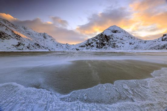 roberto-moiola-wave-advances-towards-the-shore-of-the-beach-surrounded-by-snowy-peaks-at-dawn