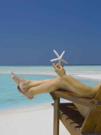 sakis-papadopoulos-woman-holding-seastar-on-the-beach-maldives-indian-ocean-asia