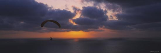 silhouette-of-a-person-paragliding-over-the-sea-blacks-beach-san-diego-california-usa