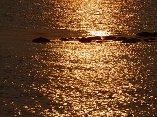 silhouettes-of-rocks-on-dark-water-sparkling-with-golden-sunshine