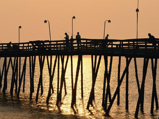 steve-winter-people-on-a-pier-are-silhouetted-at-twilight