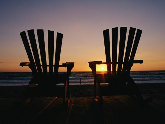 steve-winter-two-chairs-on-a-shoreline-facing-the-setting-sun