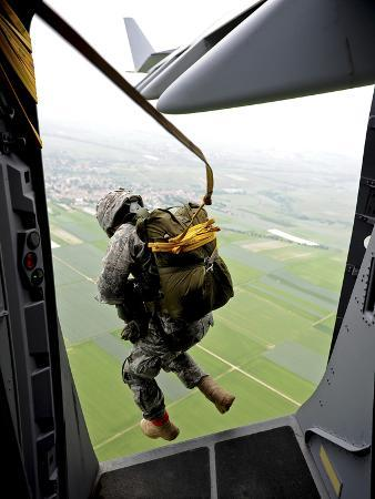 stocktrek-images-a-paratrooper-executes-an-airborne-jump-out-of-a-c-17-globemaster-iii