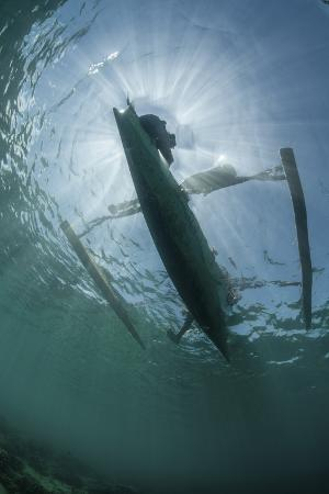 stocktrek-images-a-wooden-outrigger-near-a-remote-island-in-indonesia