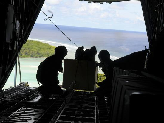 stocktrek-images-airmen-push-out-a-pallet-of-donated-goods-from-a-c-130-hercules