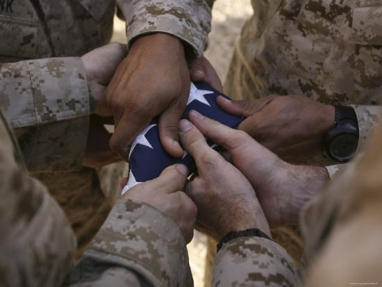 stocktrek-images-marines-fold-an-american-flag-after-it-was-raised-in-memory-of-a-fallen-soldier