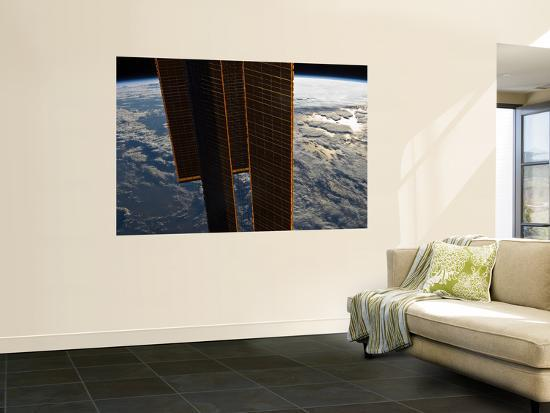 stocktrek-images-solar-panels-of-the-international-space-station-backdropped-by-a-blue-and-white-earth
