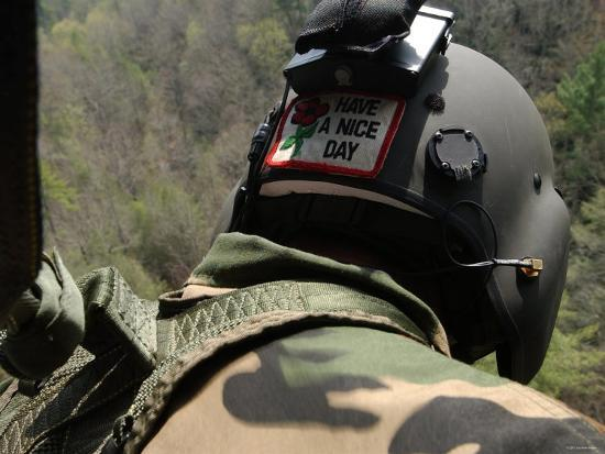 stocktrek-images-us-army-national-guardsman-looks-out-a-uh-60-black-hawk-helicopter-during-a-search-and-rescue