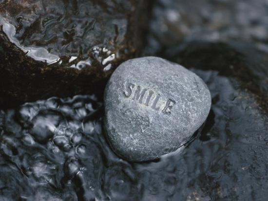 stone-with-word-smile-in-water-of-tranquil-stream