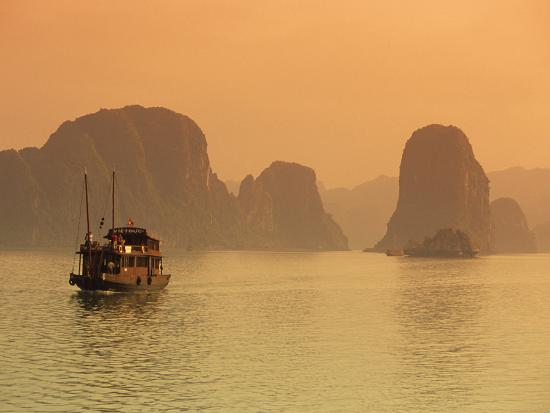 stuart-black-traditional-boat-sailing-through-limestone-archipelago-at-sunset-ha-long-bay-unesco-world-heritag