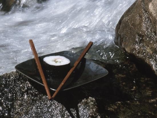 sushi-and-chopsticks-in-nature-on-boulder-near-rushing-river-water