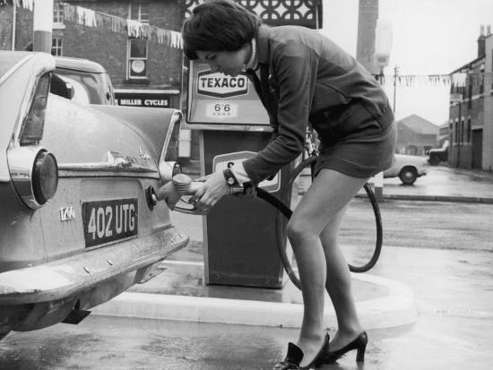 the-modern-female-petrol-pump-operator-refuelling-a-car-in-her-mini-skirt
