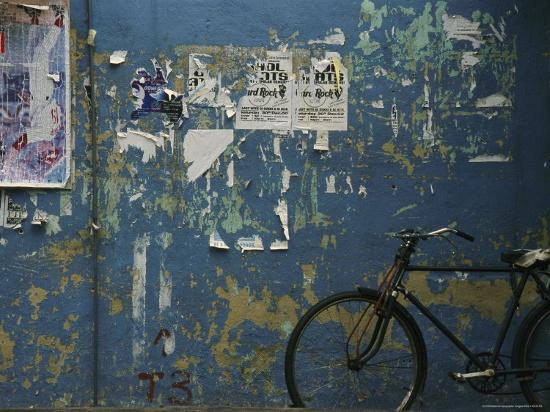todd-gipstein-a-bicycle-is-parked-against-a-blue-wall