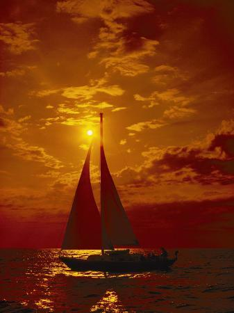 todd-gipstein-a-passing-sailboat-is-silhouetted-against-a-brilliant-orange-sunset-near-bermuda