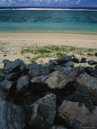 todd-gipstein-calm-surf-breaking-on-sandy-shore-with-dark-stones-in-foreground