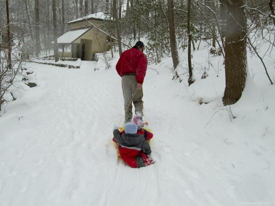 todd-gipstein-man-pulling-two-children-on-a-sled-through-the-snow