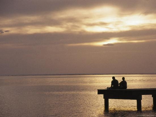 todd-gipstein-two-people-fishing-on-a-pier-looking-out-at-sunset-over-the-pacific-ocean