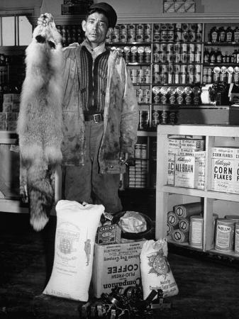 trapper-archie-pouder-holding-up-his-catch-at-the-hudson-s-bay-company-trading-post-store